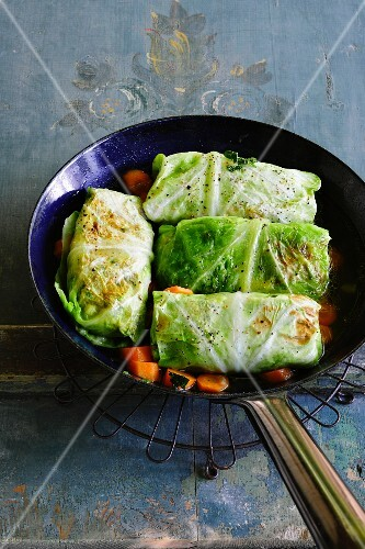 Cabbage parcels in a pan with steamed carrots