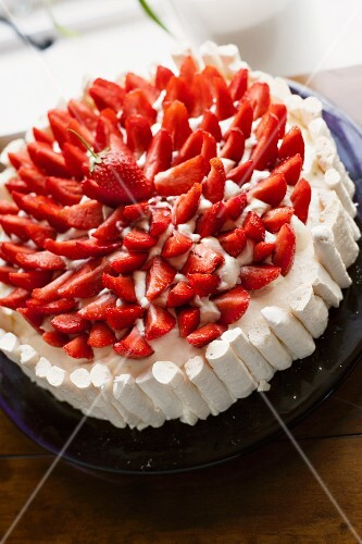 A strawberry cake with a meringue edge