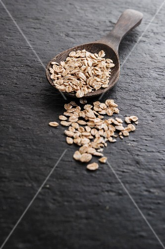Oats on and next to a wooden spoon