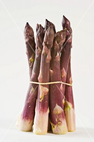 A bunch of purple asparagus against a white background