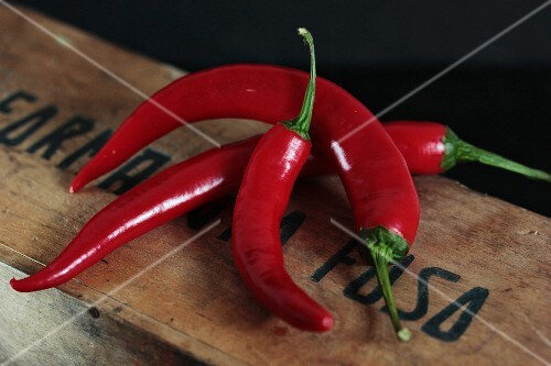 Three chilli peppers on a wooden crate