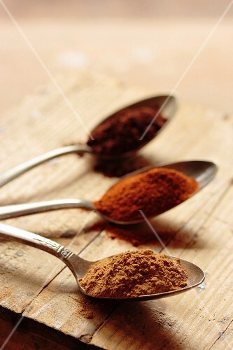 Cinnamon, paprika and cocoa on three silver spoons on a wooden surface