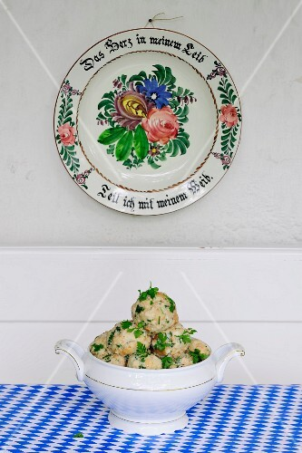 Bread dumplings with parsley in a round terrine underneath an old-fashioned painted plate hanging on the wall