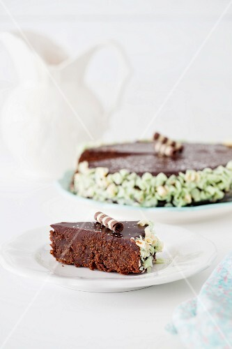 A chocolate cake with chocolate glaze (a slice in the foreground and the rest of the cake in the background)