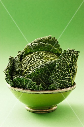 A savoy cabbage in a green bowl