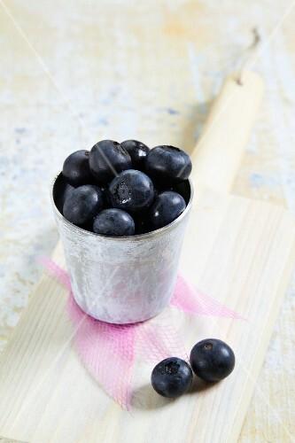 A mug of fresh blueberries on a chopping board