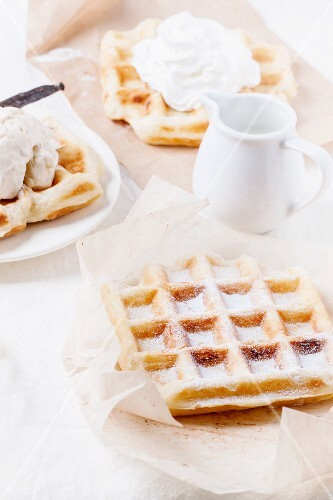 Belgian waffles served with whipped cream, ice cream, icing sugar and a jug of milk