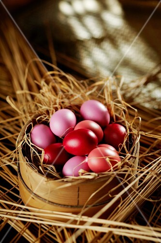 Pink and red Easter eggs in straw in a woodchip basket