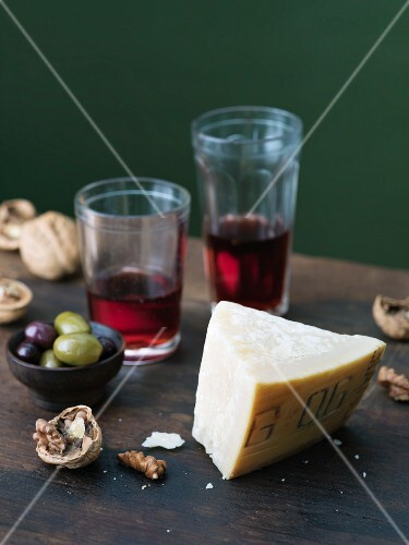 An autumnal arrangement featuring cheese, red wine, nuts and olives