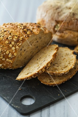 Seed bread with rolled oats, partly sliced