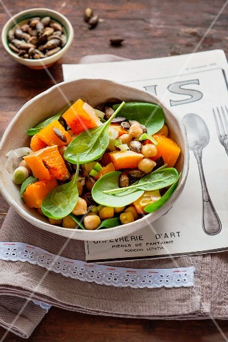 A mixed salad made with pumpkin, chickpeas, baby spinach and roasted pumpkin seeds