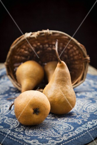Pears and a basket on a wooden table