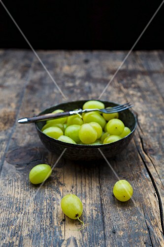 Green grapes in a metal dish on a wooden table