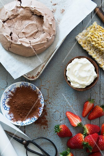Ingredients for a chocolate pavlova with whipped cream and strawberries