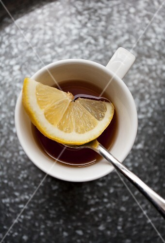 A cup of tea with a slice of lemon