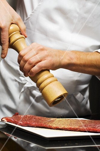 A chef seasoning beef with pepper