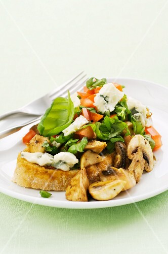 A slice of bread topped with mushrooms, tomatoes, Gorgonzola and basil