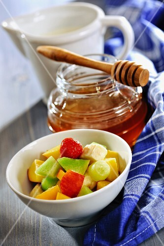 A bowl of fruit salad with a jar of honey and a jug of milk in the background
