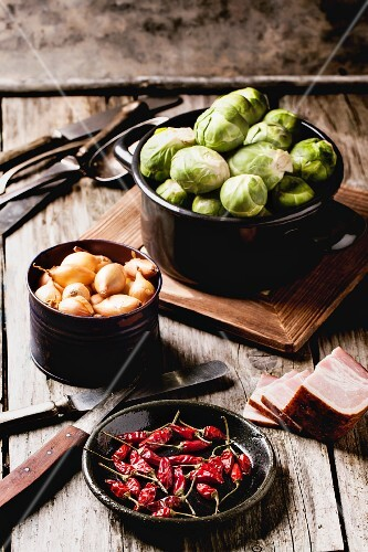 Brussels sprouts, onions, chilli peppers and bacon on an old wooden table