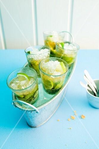 Five glasses of woodruff caipirinha in an ice bucket