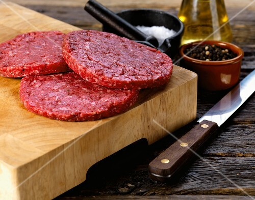 Bison burgers on a chopping board