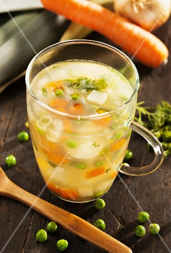 A glass of vegetable stock with carrots and peas