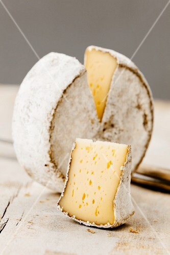 A wheel of Mutschli Swiss cheese, sliced