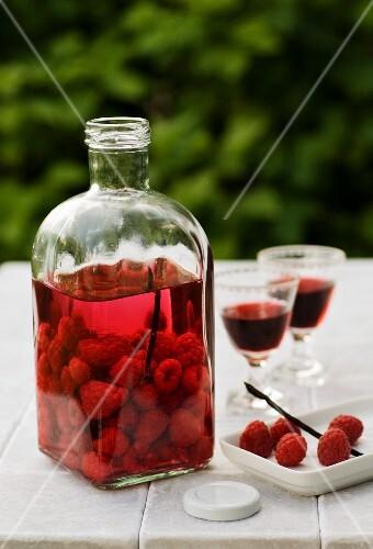 Home-made raspberry liqueur on a garden table