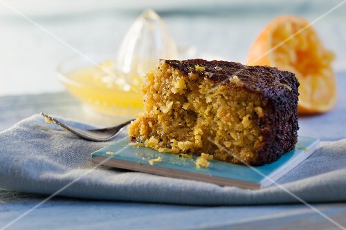 A slice of orange and almond cake with a bite taken out
