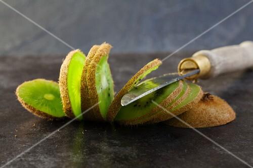 A sliced kiwi and a knife