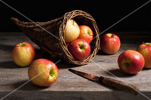 Apples in a cornucopia basket on a wooden table