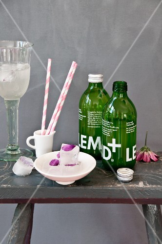 Cosmos petals frozen into ice cubes, lemonade in green bottles and stripes paper straws on rustic stool