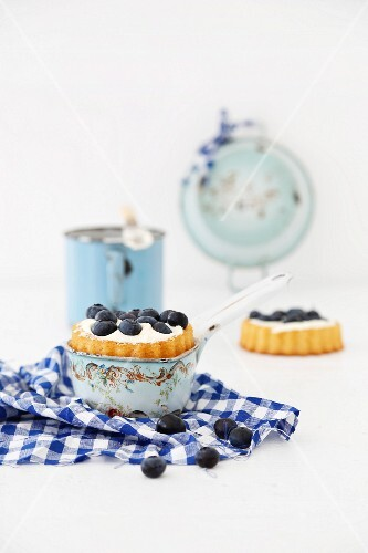 Tartlets with blueberries and cream, one in an enamel pan and one on a checked apron