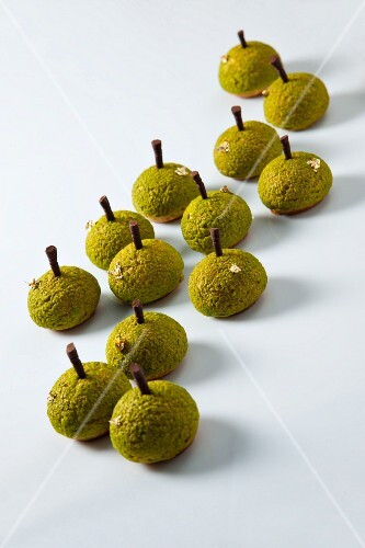 Choux pastries decorated with pistachios and gold leaf