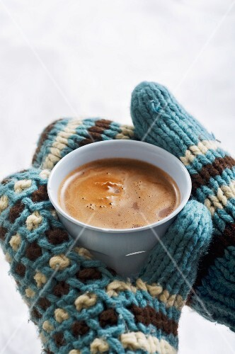 Gloved hands holding a cup of hot chocolate