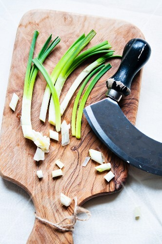 Chopped spring onions on a wooden board