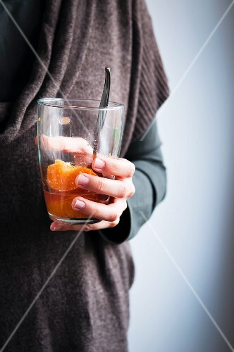 A woman holding a glass of peach compote