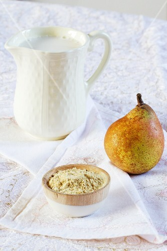 A bowl of carob bean gum, a pear and a jug of rice milk