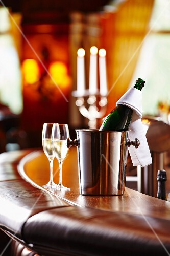 A bottle of champagne and champagne glasses on a bar