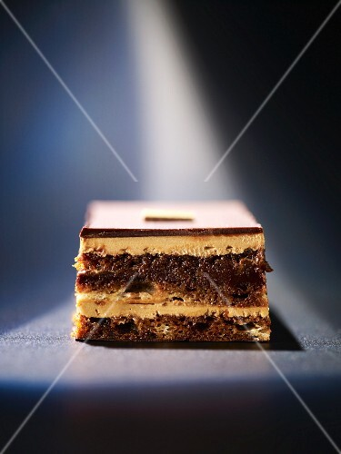 A slice of chocolate layer cake with butter cream and chocolate glaze