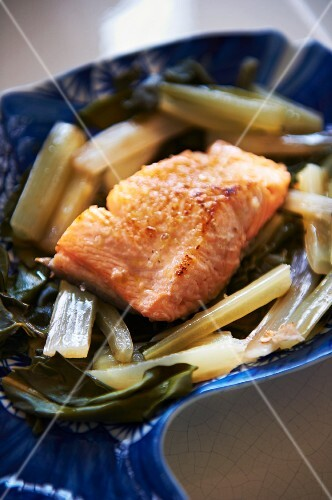 Fried salmon fillet on steamed chard on a fish-shaped plate