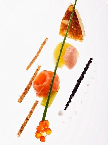 An artistic arrangement of smoked salmon, tamaras, salmon caviar and strips of toast