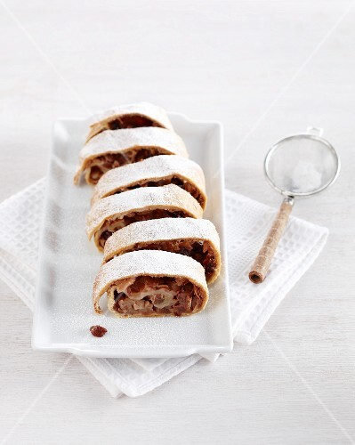 A sliced apple strudel dusted with icing sugar