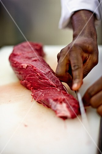 A cook removing the fat from a slice of beef