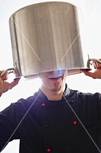 A chef holding a pot over his head