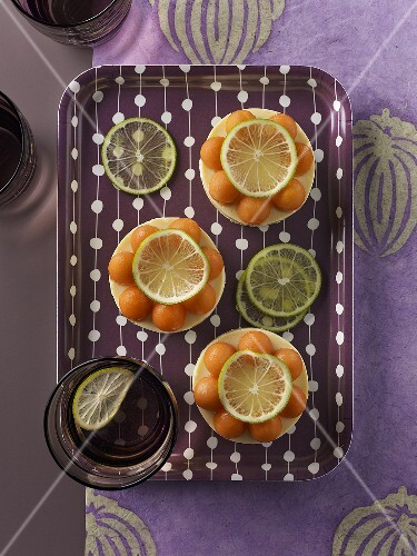 Cream cheese cakes with melon balls on a tray (seen from above)