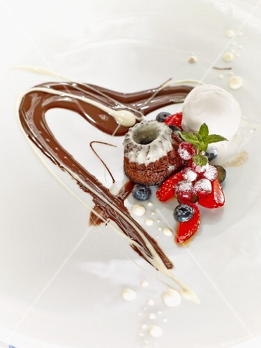 A mini cake with berries and chocolate sauce