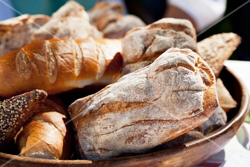 Various types of bread in a wooden bowl