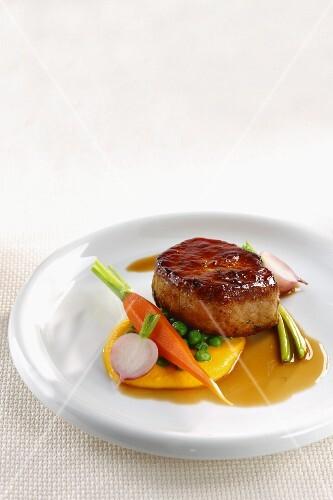A pork medallion with spring vegetables