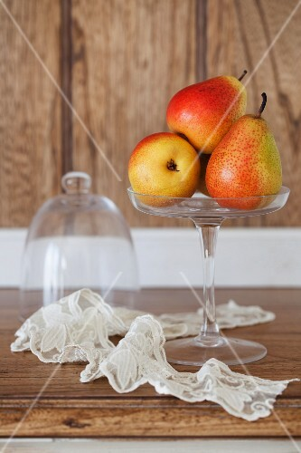 Red and yellow pears on a glass stand